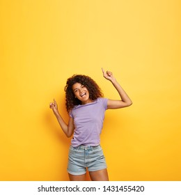 Joyous happy attractive dark skinned female with frizzy hair, raises hands to good vibed music, has slim figure, enjoys party and has fun, dances against yellow background with copy space above