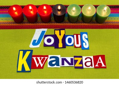 JOYOUS KWANZAA text word collage typography, seven candles and multi colored fabric on green woven fabric, African American holiday, horizontal aspect