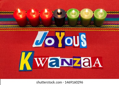 JOYOUS KWANZAA text word collage typography, with seven candles and multi colored fabric on red woven fabric, African American holiday, horizontal aspect
