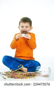 Joyous little kid eating chocolate sitting cross-legged on floor, sweets spilt. Isolated on white.