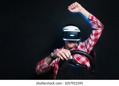 The joyous man sits in the VR glasses and plays the race on the simulator of the car. A happy gamer plays a race with a VR headset. Victory in the game