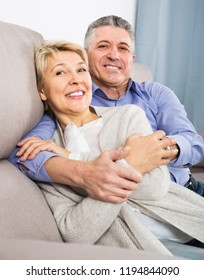 joyous mature married couple in cozy house are warmly reconciled after quarrel