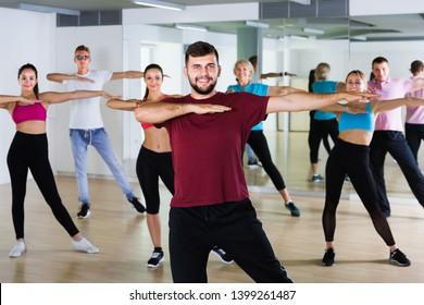 joyous men women of different ages posing in fitness studio