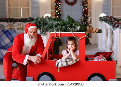 Joyous Santa Claus making thumbs up gesture near decorated house. Happy pretty female child satisfied with bought tied fir tree on top of children car. Concept of Christmas decorations and attributes.