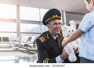 Joyous smiling aviator giving toy to boy