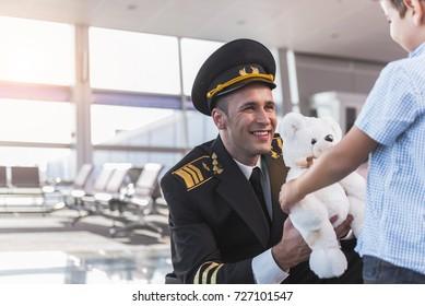 Joyous smiling aviator giving toy to boy