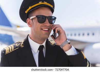 Joyous smiling pilot speaking on phone