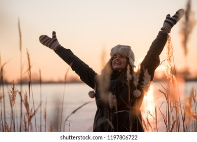 Joyous woman near frozen lake - sunset