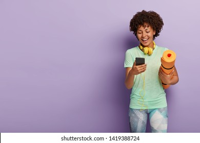 Joyous young girl has break in training, poses with fitness mat, holds smartphone, enjoys songs in headphones, wears sportswear, isolated over purple wall, copy space. Sportswoman listens music
