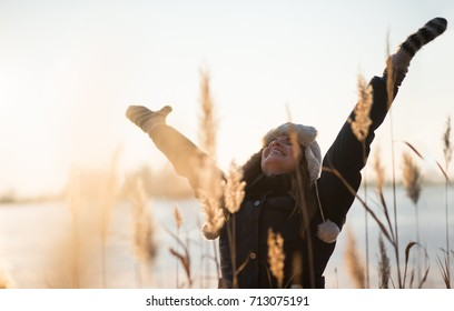 Joyous young woman with her arms raised up
