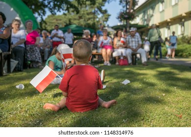 Jozefow, Poland - August 1, 2018: Children with white and red polish flag in the hand. Celebration of anniversary of the Warsaw Uprising. Polish symbols.