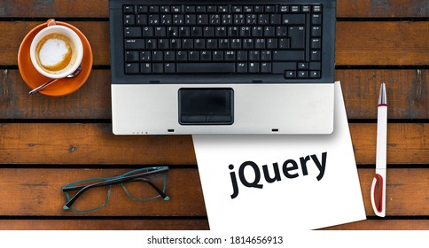 jQuery. Paper width word jQuery and laptop, glasses and coffee on wooden table