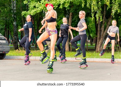 JRussia, Samara, June 2020: umping fitness. A group of girls dancing in jumpers, special boots on a spring platform in the park on a summer sunny day.