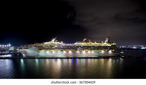 Juan, Puerto Rico - November 16, 2015: Royal Cribbean cruise line, ship Grandeur of the Seas standing in harbor with full bright illumination at night on water, horizontal picture