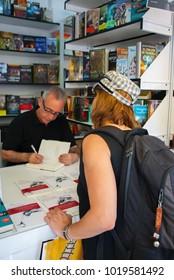 Juan José Millás signs a book to a reader at the Madrid Book Fair in June 2011