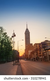 Juarez Avenue towards Latin America tower in Mexico downtown in sunrise summer sun
