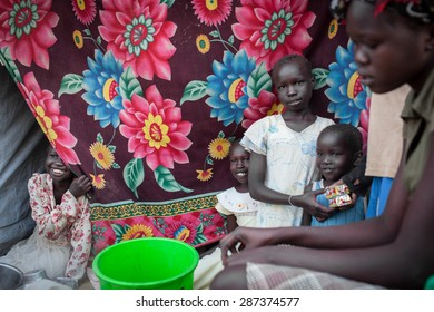 Juba, South Sudan - February 19, 2014: South Sudanese children watch their mother cook in a refugee camp