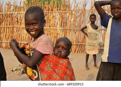 Juba, South Sudan, February 2017. Camp for internally displaced persons (IDPs). A little smiling girl is carrying her brother. Captured during civil war.