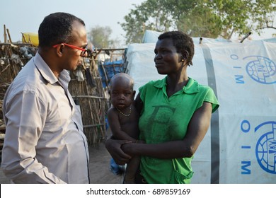 Juba, South Sudan, February 2017. Salesian priest talking to a sad woman with a baby. Camp for internally displaced persons (IDPs). Captured during civil war.