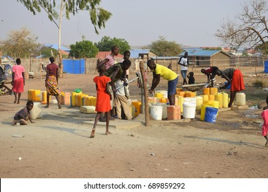 Juba, South Sudan, February 2017. People with yellow jerrycans waiting for water at a borehole site. Salesian camp for internally displaced persons (IDPs). Captured during civil war.