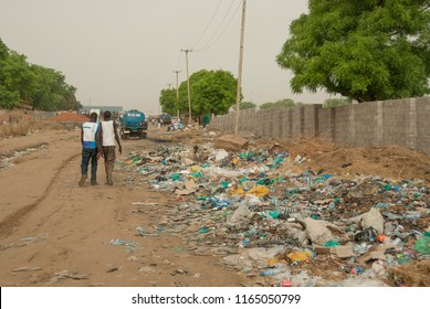 JUBA, SOUTH SUDAN - FEBRUARY 27 2012: Unidentified people pass by rubbish dump on a street in Juba, South Sudan. Recycling of plastic waste is a major problem for most African countries.