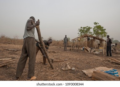 JUBA, SOUTH SUDAN - FEBRUARY 28 2012: Unidentified refugees prepare wooden log for a construction of new hovel in displaced persons camp, Juba, South Sudan. People stay in harsh conditions here.