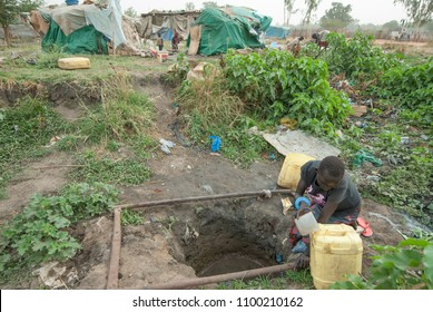 JUBA, SOUTH SUDAN - FEBRUARY 28 2012: Unidentified woman takes potable water from dirty hole in refugee camp, Juba, South Sudan. Refugees stay in harsh conditions here for long time.