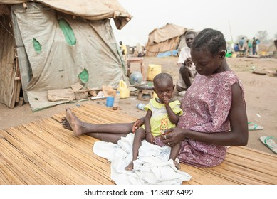 JUBA, SOUTH SUDAN - FEBRUARY 28 2012: Unidentified woman with her daughter sits in front of her hovel in displaced persons camp, Juba, South Sudan. Refugees stay in harsh conditions in camps of Juba.