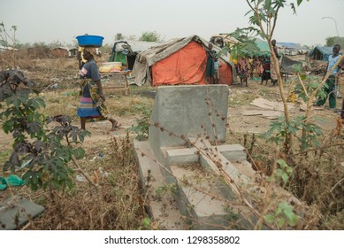 JUBA, SOUTH SUDAN - FEBRUARY 28 2012: Unidentified woman passes by stone grave on refugee camp background, Juba, South Sudan. Camp is located on abandoned cemetery and people stay in harsh conditions.