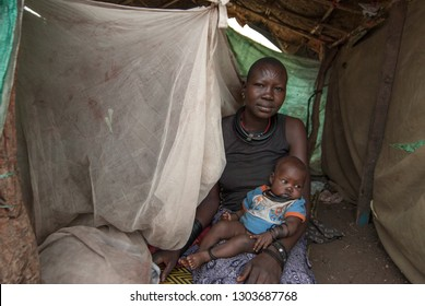 JUBA, SOUTH SUDAN - FEBRUARY 28 2012: Unidentified woman with baby sits in makeshift hovel in displaced persons camp, Juba, South Sudan. Refugees stay in harsh conditions in camps of Juba.