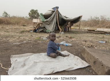 JUBA, SOUTH SUDAN - FEBRUARY 28: Unidentified kid plays with plastic bottle in front of his hovel in displaced persons camp, Juba, South Sudan, February 28, 2012. People stay in harsh conditions here.