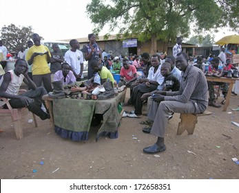 JUBA, SOUTH SUDAN - FEBRUARY 29: Unidentified shoe shiners wait for their clients at a market of Juba, South Sudan on February 29, 2012. Shoeshine is the most common type of small business in Juba .