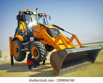 Jubail, Saudi Arabia - September 8, 2012: Maintenance of an Excavator carried out by its operator and helper