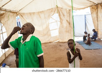 Jube, South Sudan - March 1, 2014: A South Sudanese man swallows anti-cholera medication
