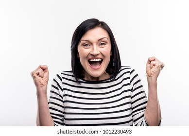 Jubilant mood. Overjoyed young woman clenching her fists and raising her hands in a triumphant movement while shouting joyfully