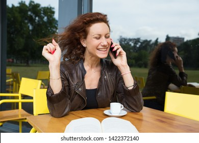 Jubilant woman closing eyes from excitement when receiving good news. Cheerful petty young woman talking on phone when sitting alone at sidewalk cafe. Achievement concept