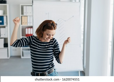 Jubilant young businesswoman rejoicing and cheering after a personal success or good news in front of a flip chart in the office