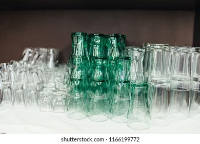 juce glass . Close up empty glasses on the showcase in restaurant, prepare for dinning room.Pile of clean glasses.dry, transparent glasses stand in a row upside down.Selective focus