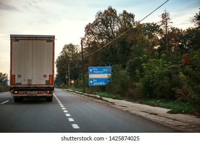Jucu, Romania - Sep 26, 2013: Romanian highway with large truck cargo haulage near street road sign featuring almost visible NOKIA sign after Nokia Finland closed the factory near Cluj in 2011