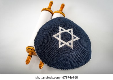 Judaism and jewish religious holiday concept with a closed Torah and a kippah also called a yamaka. Some of the better known jewish holidays are Tisha B'Av, Purim, Hannukah, Yom Kippur, etc