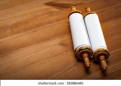 Judaism and religious text concept with a closed Torah on wooden background with copy space