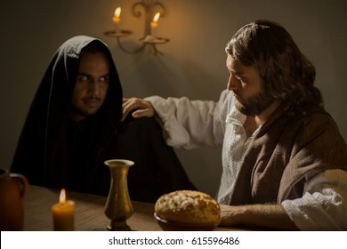 Judas looking at Jesus Christ with evil look during the last supper
