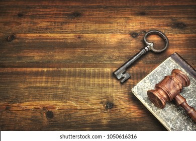 Judge Gavel Or Auctioneer Hammer, Old Door Key, Law Books On The Vintage Wooden Background. Overhead View. Law Concept.