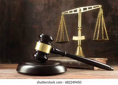 Judge gavel, book and scales on the wooden lawyers desk, justice symbols for social balance in law and court, dark background with copy space, selected focus, narrow depth of field