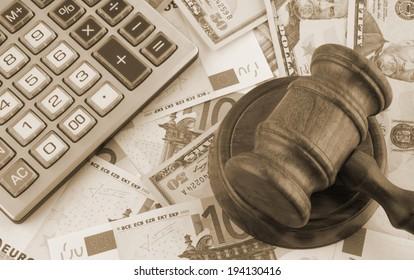 Judge gavel, calculator and euro and dollar banknotes