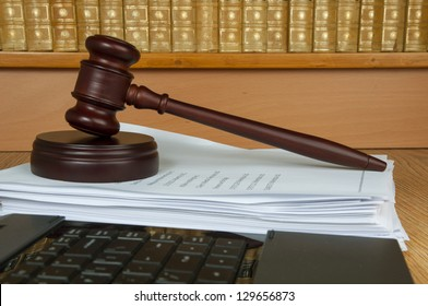 Judge gavel with computer and old legal books in the background