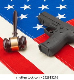 Judge gavel and hand gun over USA flag - studio shot
