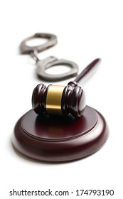 judge gavel with handcuffs on white background