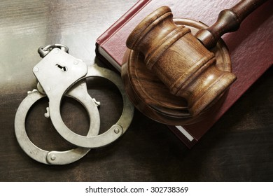 Judge gavel and handcuffs with red legal book on wooden table