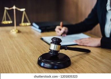 Judge gavel with Justice lawyers, Businesswoman in suit or lawyer working on a documents. Legal law, advice and justice concept.